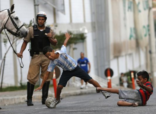Kids play soccer on a street as a police officer watches outside Indepedencia stadium before the start of the Argentine national team training session in preparation for 2014 World Cup in Belo Horizonte