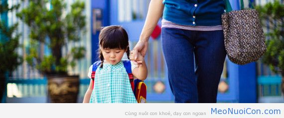 Toddler girl in uniform holding hands with mom